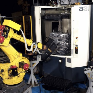 A Robot loading parts on to the Hydraulic Fixture within the work area of the Machining Center.